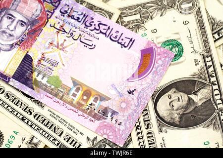 Eine Nahaufnahme Bild eines bunten Ein rial Bank Note aus Oman auf einem Bett von amerikanischen Dollarnoten in Makro - Stockfoto