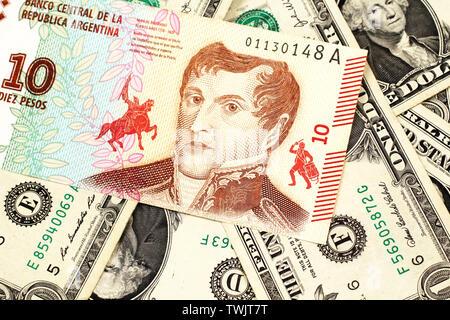 Eine Nahaufnahme Bild eines 10 Peso Bank Note aus Argentinien auf einem Bett von amerikanischen Dollarnoten in Makro - Stockfoto