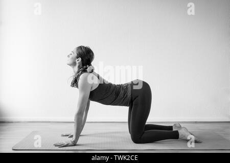 Seitenansicht einer jungen Frau, die die Kuh Pose oder Bitilasana yoga Pose in Ihrem Haus. - Stockfoto