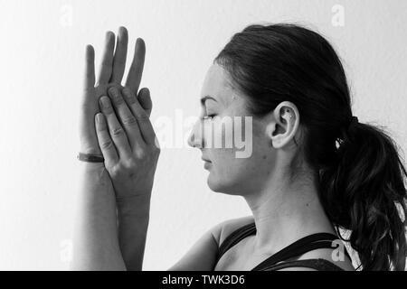 Close-up Seitenansicht eines brünette Frau in Ihrem 30 macht die Sitzung eagle Asana oder Yoga darstellen, zu Hause. Horizontales Format. - Stockfoto