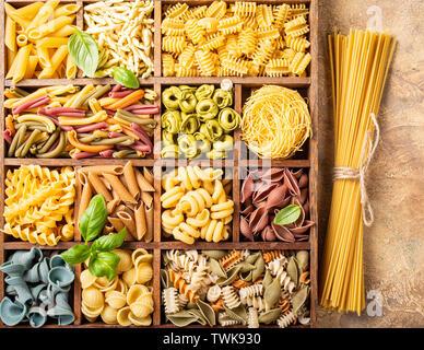 Spaghetti und sortierte Bunte italienische Pasta in Holzkiste. Gesundes essen Hintergrund Konzept. Flach, Ansicht von oben. - Stockfoto