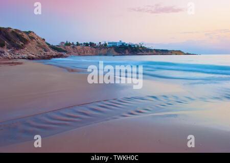 Anzeigen von leeren Sandstrand Coral Bay Beach in der Nähe von Paphos, raucherregelung. Sonnenuntergang, rosa Himmel über hellblau Flachwasser mit Wellen, Villen auf der Klippe. Warmen Abend - Stockfoto