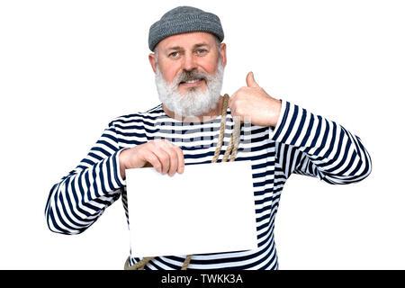Foto Seemann in einem gestreiften T-Shirt. Ein Mann mittleren Alters mit einem grauen Bart ist ein weißes Blatt Papier - Stockfoto
