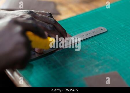 Qualifizierte Erwachsene afrikanischer Mann Messen und Schneiden Leder auf einem Tisch. - Stockfoto