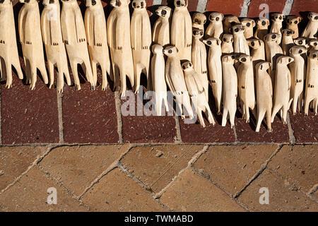 Tierfiguren, die dem aus Holz geschnitzten Meerkat ähneln und als Souvenirs der afrikanischen Tierwelt auf einem lokalen Straßenmarkt in Südafrika verkauft werden. - Stockfoto