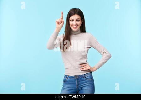 Studio Porträt einer wunderschönen kaukasische Frau, Finger nach oben, in die Kamera lächeln suchen, Arms akimbo, auf blauem Hintergrund isoliert - Stockfoto
