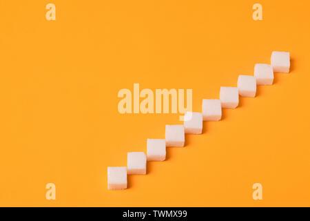 Leiter von würfelzucker über orange Hintergrund - Stockfoto