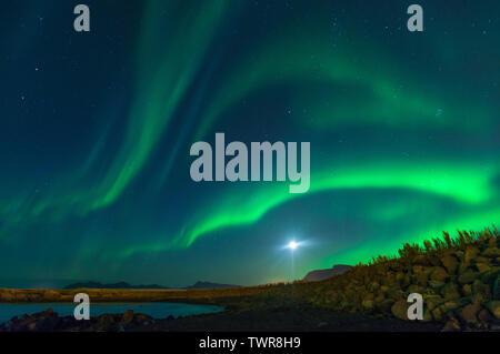 Mond mit northern lights Display in Island. Bunte Himmel bei Nacht, Wellen der grünen Aurora borealis Malerei der blauen Nachthimmel. - Stockfoto