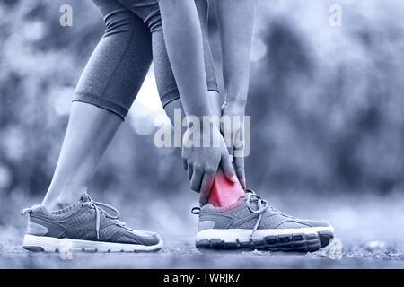 Gebrochene Knöchel verdreht - laufende sport Verletzung. Läuferin berühren Fuß in Schmerzen aufgrund von verstauchten Knöchel. - Stockfoto