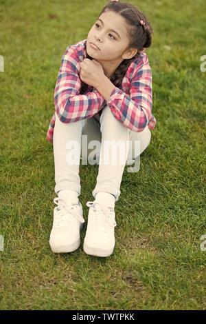 Cute daydreamer. Mädchen kleines Kind verbringen Freizeit draußen im Park. Mädchen sitzen auf Gras im Park. Kind genießen Sie Frühling sonniges Wetter beim Sitzen an der Wiese im Park. Frühling Konzept. Park und Garten. - Stockfoto