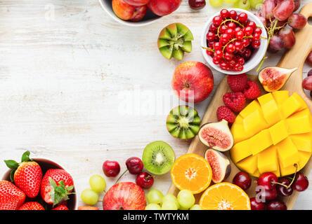 Bunte Früchte Hintergrund, Mango, Erdbeeren Himbeeren orangen Pflaumen Äpfel, Kiwis, Weintrauben, Kirschen, Blaubeeren auf weißer Tisch, zu kopieren, zu - Stockfoto