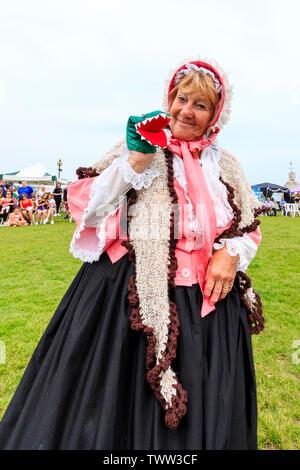 Broadstairs Dickens Festival. Die Menschen gekleidet in viktorianischen Dickensian Kostüme. Ältere Frau für Viewer posiert und ihre Marionette Drache halten, während sie lächelnd. Trägt die volle Viktorianische Kleid und Schal. Stockfoto