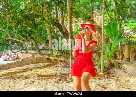 Glücklich lifestyle touristische Frau im roten Kleid schwingend am tropischen Strand unter Kokospalmen mit einer Frucht trinken. Sommer tropisches Urlaubsziel - Stockfoto