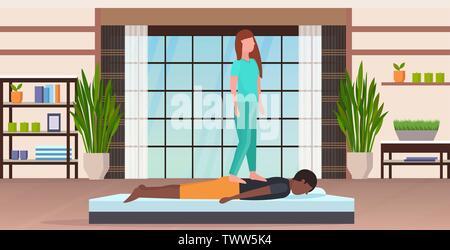 Masseurin stehend auf dem Rücken des Patienten tun Heilung ...