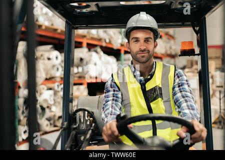 Lächelnd Gabelstapler Fahrer Lagergüter in einem Warenlager. - Stockfoto