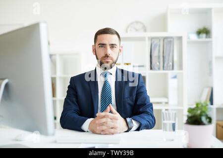Porträt von Ernst zuversichtlich hübscher junger Bartgeier Business Executive am Tisch sitzen mit Computer im Büro - Stockfoto