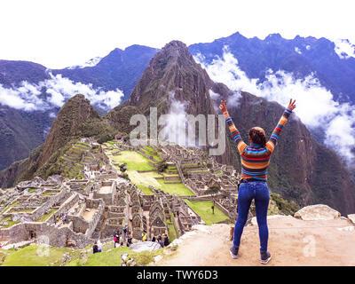 Junge Frau mit erhobenen Armen auf dem Hintergrund von Machu Picchu. Alte Inkastadt, Peru - Stockfoto