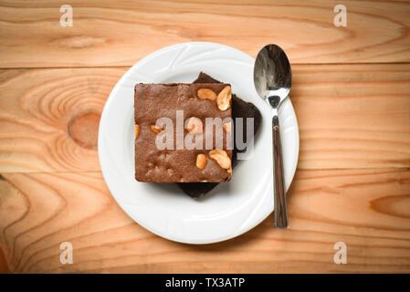 Brownies Kuchen auf dem Tisch/Chocolate Cake Slice mit der Mutter in der Platte mit Löffel auf Holz- Hintergrund - Stockfoto