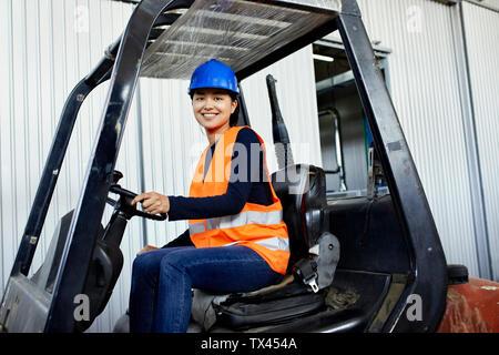 Portrait von zuversichtlich Arbeiterin auf Gabelstapler in der Factory - Stockfoto