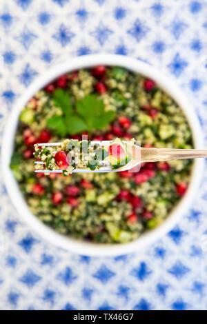 Bulgur Kräuter tabbouleh mit Granatapfel Samen auf Gabel, close-up - Stockfoto