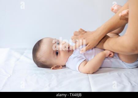 Baby Boy Zahnen. Kleine 6-monatiges Baby haben Zähne schmerzen. Mutter reiben Gel auf die Zähne ihr kleines Baby Boy. Medizin und Gesundheit Konzept.