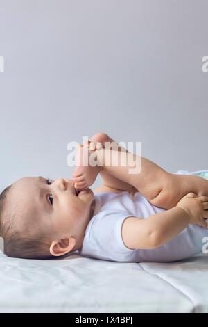 Wenig hungrig baby boy, die Füße in den Mund. 6-monatiges Baby Spaß in weißer Bettwäsche. Cute Baby liegend auf dem Bett. Familie, neue Leben, Kindheit Konzeption. - Stockfoto