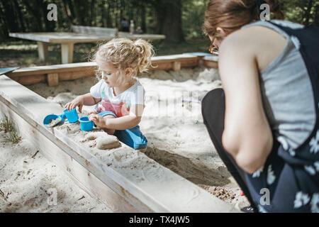 Mutter spielt mit kleiner Tochter in den Sandkasten auf dem Spielplatz