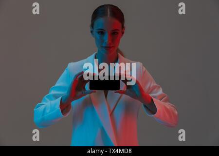 Bild Nahaufnahme der brünette Frau 20 s Holding Handy und zeigt einen schwarzen Bildschirm beim Stehen unter Neonlicht isoliert über grauer Hintergrund - Stockfoto