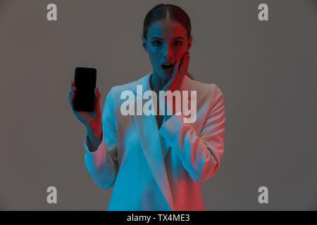 Bild Nahaufnahme von trendy Frau 20 s Holding Handy und zeigt einen schwarzen Bildschirm beim Stehen unter Neonlicht isoliert über grauer Hintergrund - Stockfoto