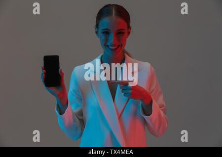 Bild Nahaufnahme von Mode Frau 20 s Holding Handy und zeigt einen schwarzen Bildschirm beim Stehen unter Neonlicht isoliert über grauer Hintergrund - Stockfoto