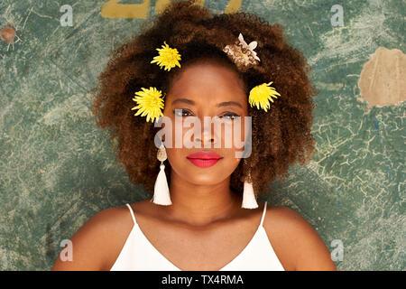 Porträt der jungen Frau mit roten Lippen tragen Ohrringe und Blumen im Haar Stockfoto