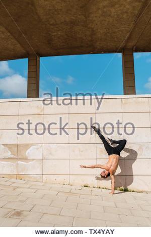 Junger Mann macht einen handstand an der Wand im Freien - Stockfoto