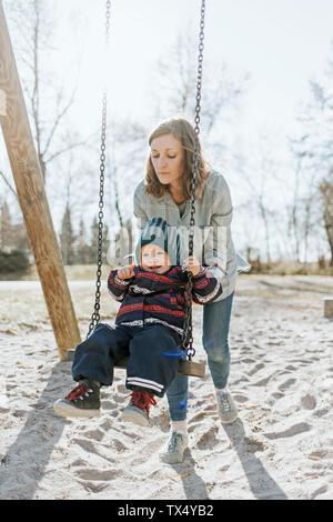 Mutter mit Tochter auf Schaukel auf dem Spielplatz
