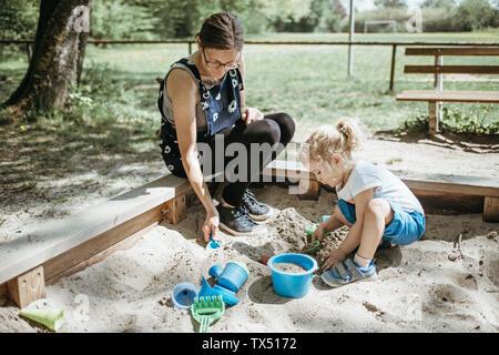 Mutter spielt mit kleiner Tochter in den Sandkasten auf dem Spielplatz - Stockfoto