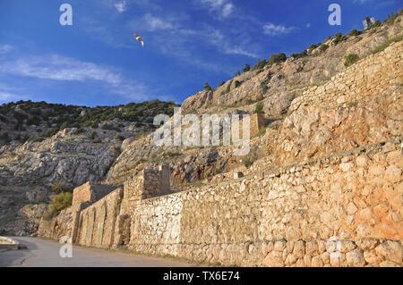 Die alte Stein befestigten Mauer in den Bergen gegen den blauen Himmel hoch steht und der fliegenden Weißen Möwe
