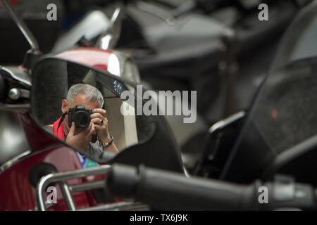 Paris, Frankreich, 05.Juli 2018: Ein Fotograf nimmt seine selfie Im Rückspiegel eines Motorrads geparkt auf einer Straße in Paris. - Stockfoto