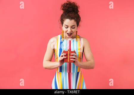 Happy intrigiert hübsche rothaarige Frau in Kleid holding Geschenkkarton mit offenen Mund über rosa Hintergrund - Stockfoto
