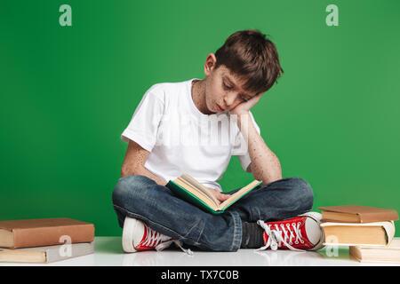 Süße kleine Junge mit den Sommersprossen studieren, Sitzung mit Stapel von Büchern über grüner Hintergrund - Stockfoto