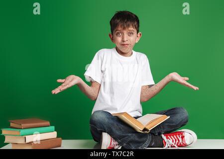Süße kleine Junge mit den Sommersprossen studieren, Sitzung mit Stapel von Büchern über grünen Hintergrund, Lesen - Stockfoto