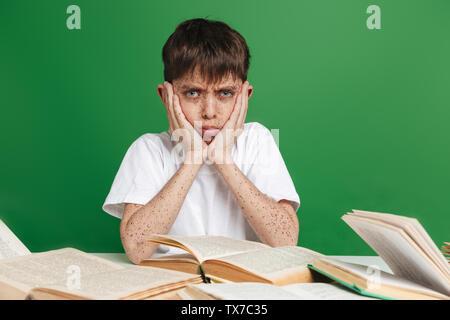 Verwirrt Cute little boy mit Sommersprossen studieren, Sitzung mit Stapel von Büchern über grüner Hintergrund - Stockfoto