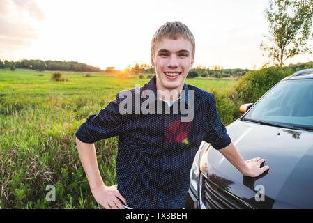 Glückliche junge Mann gegen sein Auto gelehnt neben einem offenen Feld bei Sonnenuntergang. - Stockfoto