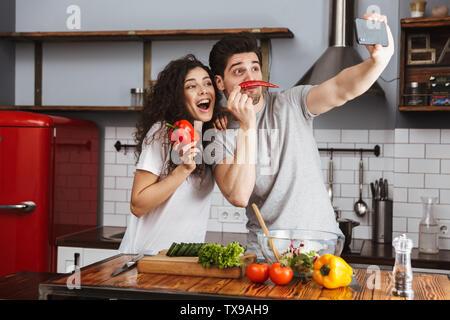 Bild der kaukasischen Paar Mann und Frau 30 s unter selfie Foto beim Kochen Salat mit Gemüse zusammen in der modernen Küche zu Hause. - Stockfoto