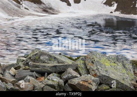 Gerahmte Blick des Auges Lake im Rila Gebirge, von bunten, Risse im Eis, von Moos bedeckt Vordergrund Felsen und Hintergrund Cliff von Schnee bedeckt
