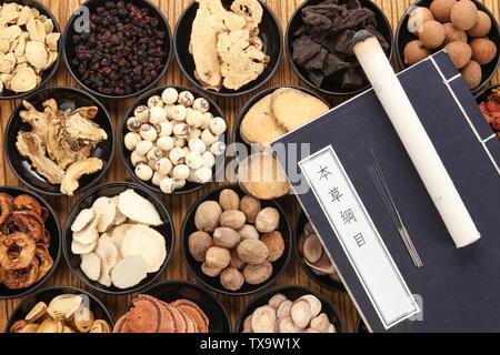 Traditionelle chinesische Medizin und medizinische Bücher auf dem Tisch.