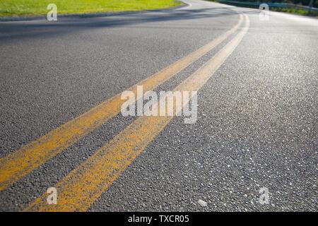 Asphaltstraße mit gelben Linien und grünes Gras an der Seite. Selektiver Fokus Straße Reise und Verkehr Konzept - Stockfoto