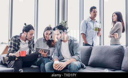 Kreative, Designer sitzen, entspannen Sie sich und sprechen auf Sofa im Büro. Tak eine Kaffeepause. - Stockfoto