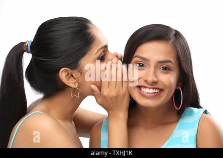 Teenager-Mädchen ein Geheimnis ihrer Freundin Flüstern - Stockfoto