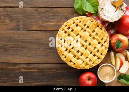 Hausgemachte Apfelkuchen mit Gitter oben und Zutaten zum Kochen auf hölzernen Tisch. Traditionelle amerikanische saisonale Gebäck Konzept mit kopieren. - Stockfoto