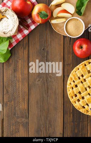 Gebackene Apfelkuchen und Zutaten zum Kochen - Zucker, Mehl, Äpfel, Zimt auf Holztisch. Saisonale Gebäck Hintergrund mit Kopie Raum für Rezept. - Stockfoto