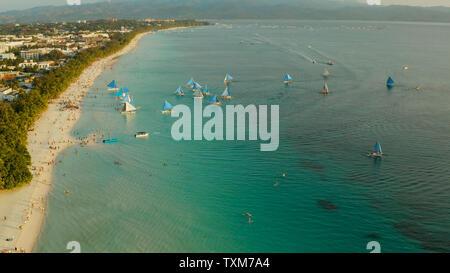 Aktuelles White Beach von oben bei Sonnenuntergang mit Touristen und Segelyachten auf der Insel Boracay. Tropischen Strand mit Segelboot. Sommer und Reisen Urlaub Konzept. - Stockfoto